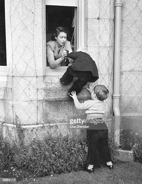 Queen Elizabeth II and Charles Prince of Wales helping Princess Anne through an open window at Balmoral Castle Scotland