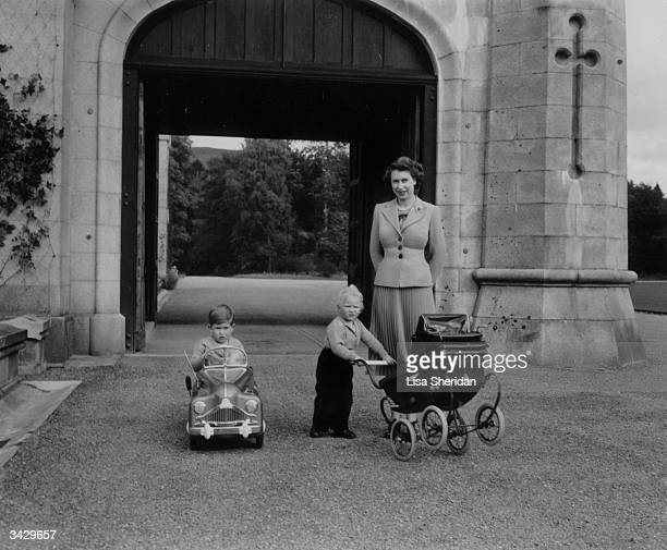 Queen Elizabeth walking with her children Charles and Anne in the grounds of Balmoral Castle in Scotland