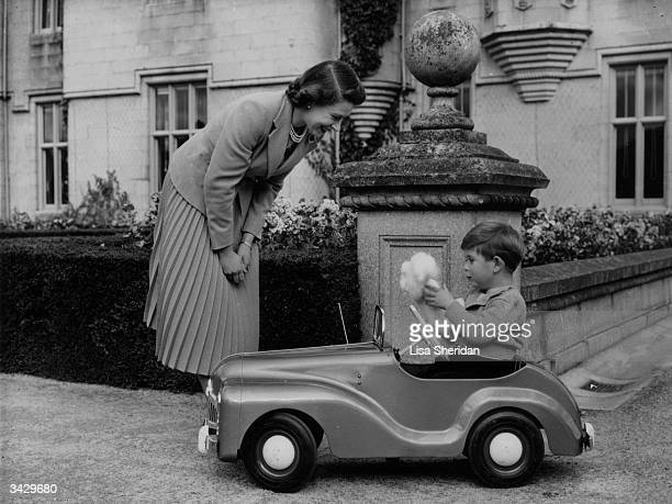 Queen Elizabeth watches her son Charles playing in a miniature car in the grounds of Balmoral Castle Scotland
