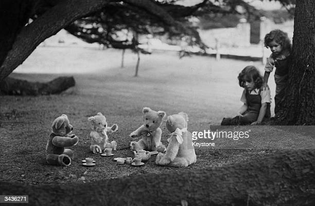 Ghislaine and Ceres Randall watching their teddy bears enjoy a picnic in Wells Somerset