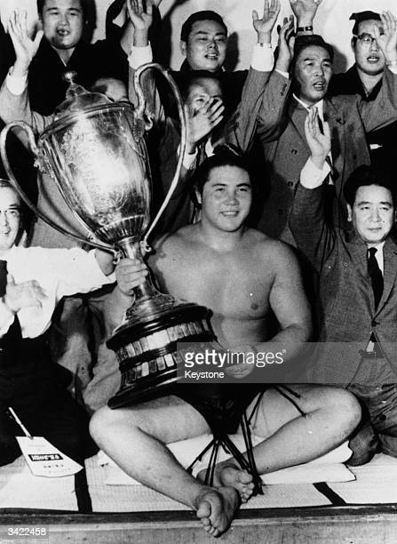 Twentyone year old Taiho Koko with the Emperor Cup which he won by defeating Grand Champion Kashiwado His victory probably means he will be made a...