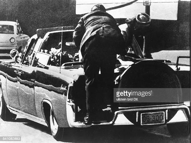 *Politiker Demokraten USA35 USPräsident 19611963ein Sicherheitsbeamter beugt sich über den von den Kugeln des Attentäters getroffenen Präsidenten...