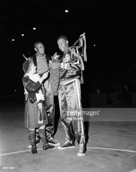 Two members of the Harlem Globetrotters basketball team receive a set of bagpipes with a member of the Dagenham Girl Pipers at Wembley Stadium