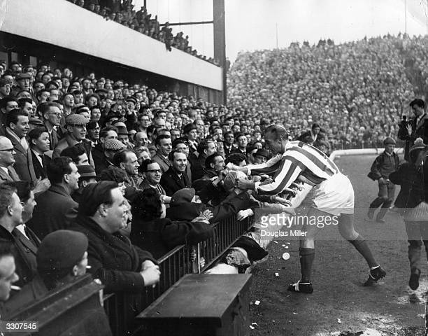 Sir Stanley Matthews aged 50 presents a souvenir ball to the spectators before playing a farewell match for the Stanley Matthews XI against a World...