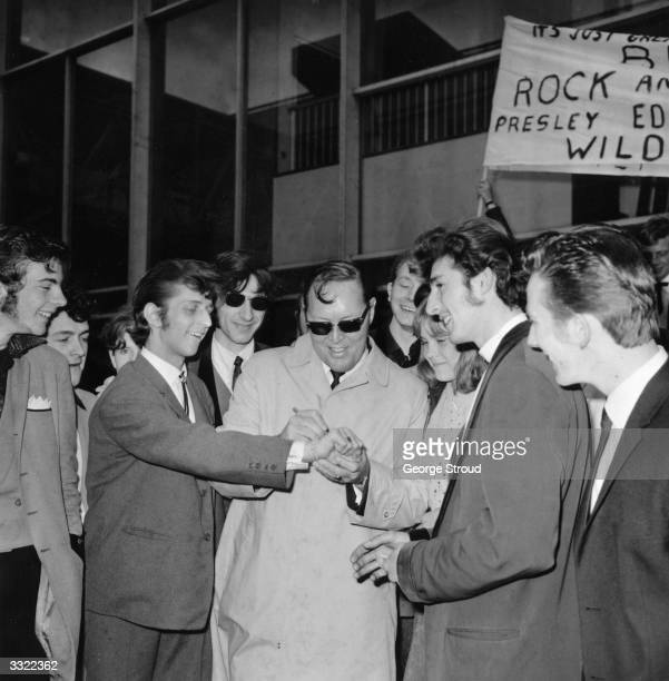 American rock 'n' roll star Bill Haley being greeted by British teddyboys and fans at London Airport