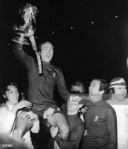 Ron Harris captain of Chelsea holds up the FA Cup trophy as he is chaired by teammates Ian Hutchinson Peter Houseman Hinton and David Webb Chelsea...