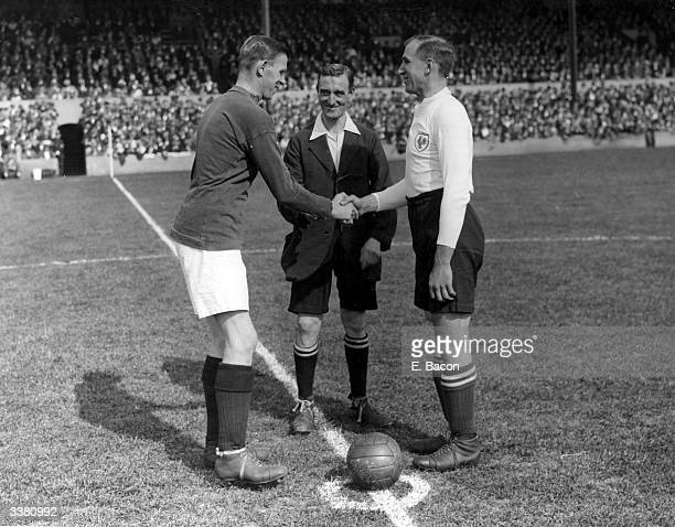 The respective team captains of Arsenal and Tottenham Hotspur Charles Murray Buchan and Arthur Grimsdell shake hands infront of the referee before...