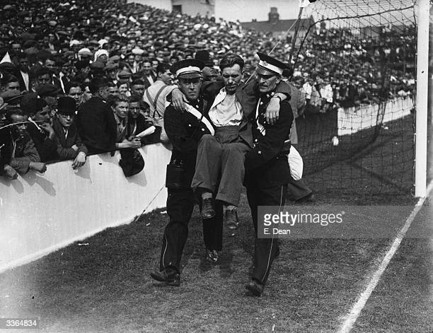 St John's Ambulancemen carry off a casualty of the heat at a football match between West Ham United and Tottenham Hotspur at Upton Park