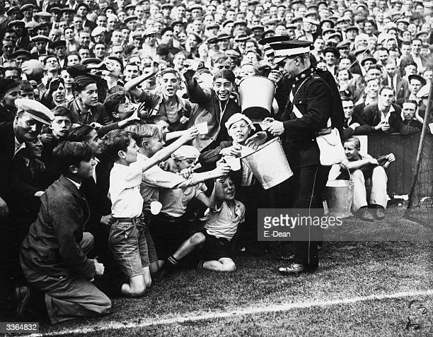 St John's Ambulancemen handing out oatmeal drinks in the heat at the football match between West Ham United and Tottenham Hotspur at Upton Park