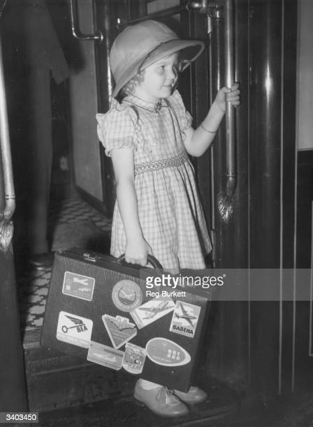 Four year old Australian girl Karin Henning Jensen wears a sun helmet and carries her labelled suitcase as she leaves for Australia from Waterloo...