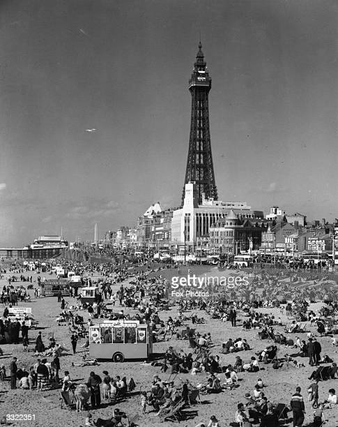 Crowds of holidaymakers on the beach at Blackpool Lancashire with the famous Blackpool Tower in the background