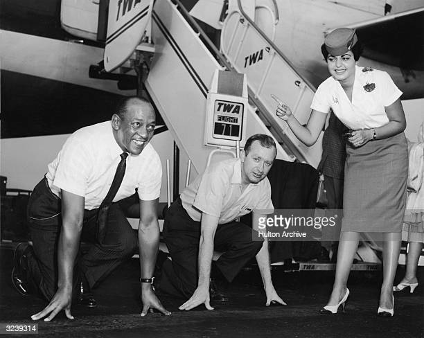 American athlete Jesse Owens prepares to race former track athlete and TWA agent John Joe Barry as TWA hostess Donna San Frankie keeps time on a...
