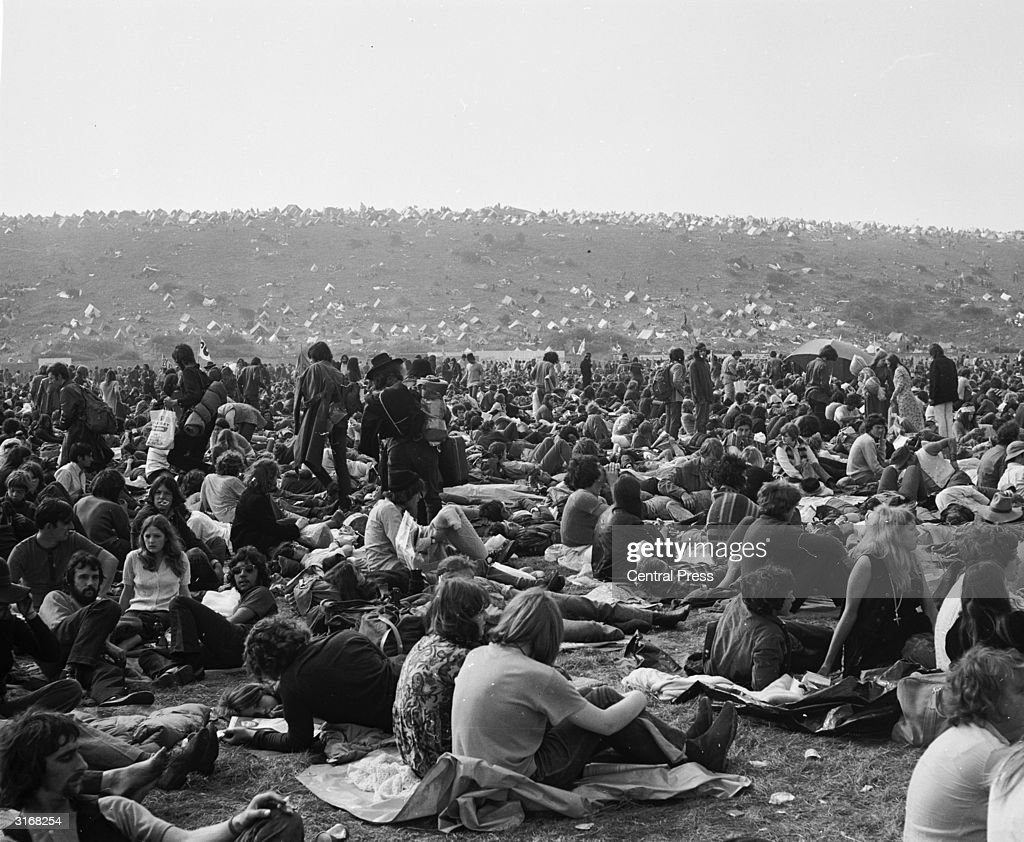 Fans sitting on the grass at East Afton Farm during the Isle of Wight Festival The camp site stretches into the distance behind them