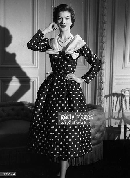 A 'readymade' afternoon dress designed by Jacques Fath polka dotted with long sleeves tight waist and muslin shawl collar Original Publication...
