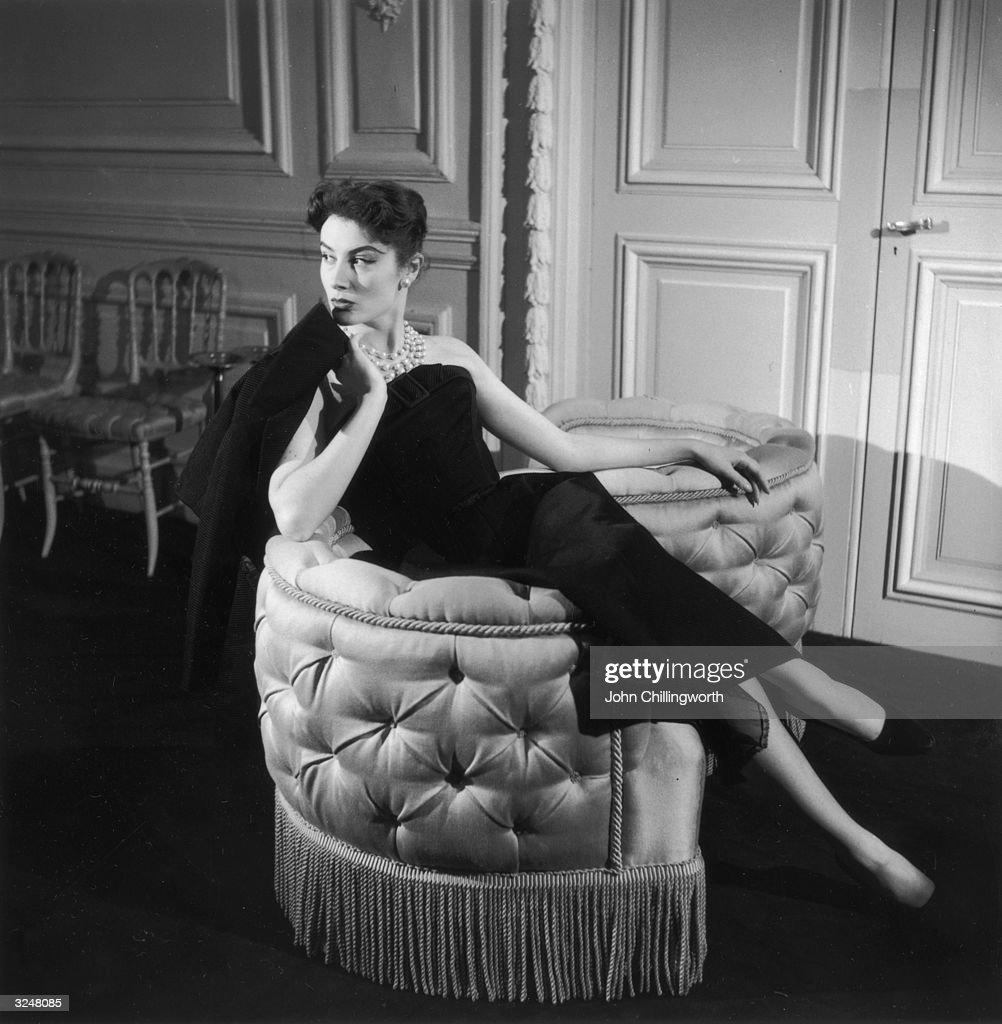 Genevieve Fath lounges in a loveseat, wearing an outfit designed by her late husband, Jacques Fath. Original Publication: Picture Post - 7496 - The House That Fath Built - pub. 1955