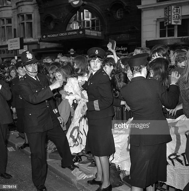 Policemen and women hold back excited young Beatles fans outside the London Pavilion in Piccadilly where the premiere of the new Beatles film 'Help'...