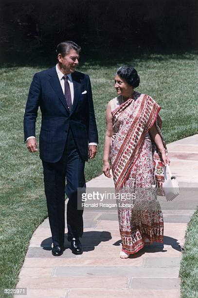 Fulllength image of US president Ronald Reagan walking with Indian prime minister Indira Gandhi along a stone path Washington