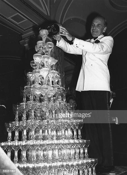 A waiter pours champagne into a tower of glasses to celebrate the opening of a new Casino at the Ritz Hotel London