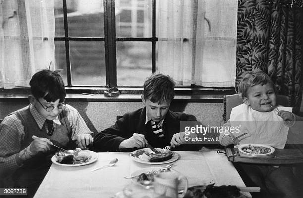 On the left 12 year old Victor Yorke and on the right his two year old brother Colin eating a meal with Stanley who lives in Harold Wood Hall the...