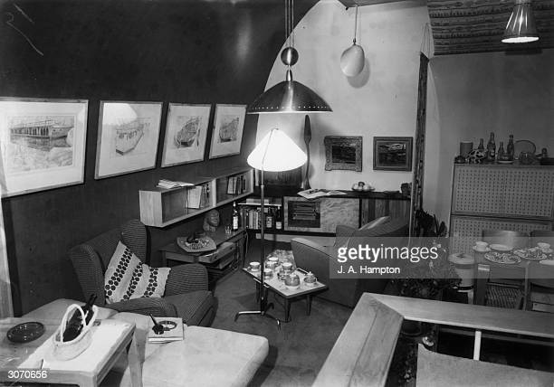 A crowded living room on show at the Tea Centre Regent Street London Wall units house china gramophone records and family papers The furniture...