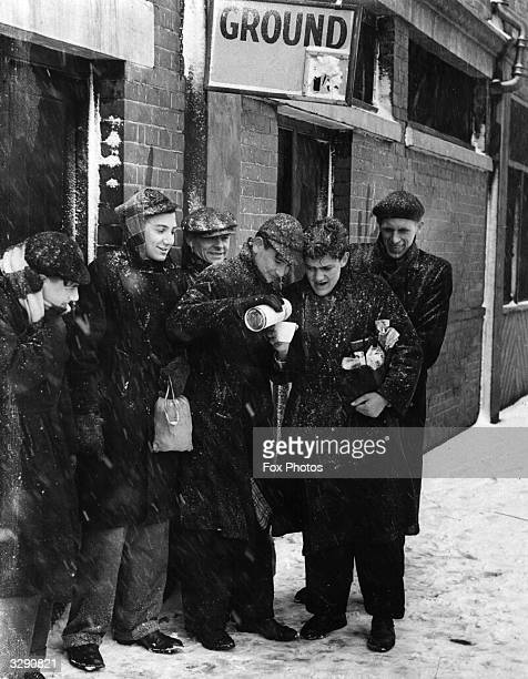 Fans arriving in the inclement weather at Tottenham's ground warm themselves with a cup of tea from a thermos They are waiting for the semi final of...