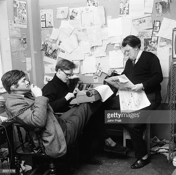 From left to right editor Richard Ingrams Christopher Booker and actor cartoonist and broadcaster William Rushton members of the staff of satirical...