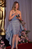 American actor Jodie Foster smiles and holds her Best Actress Oscar in front of a blue curtain at the Academy Awards Los Angeles California She won...