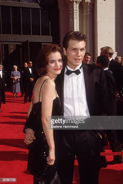 American actors Christian Slater and Winona Ryder pose while holding hands on the red carpet as they attend the Academy Awards at the Shrine...