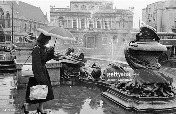 A woman walks past a fountain in the centre of Bristol Original Publication Picture Post 7170 The Best and Worst of British Cities 5 Bristol Straight...
