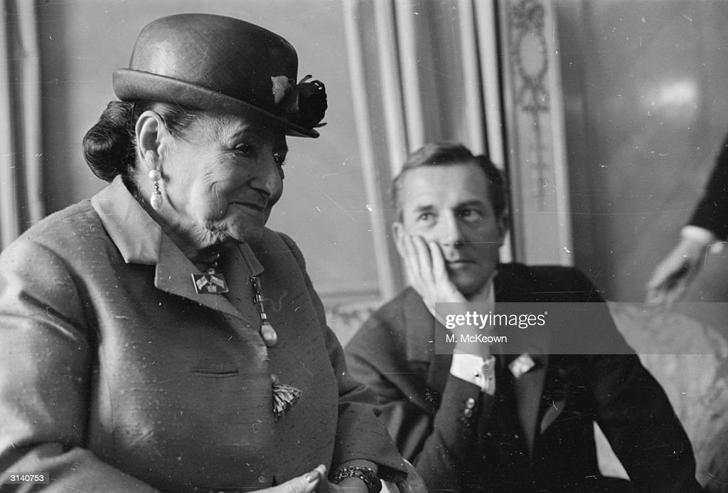 Polish born cosmetics tycoon Helena Rubinstein (1870 - 1965) and English couturier and dressmaker to the Queen, Hardy Amies (1909 - 2003).
