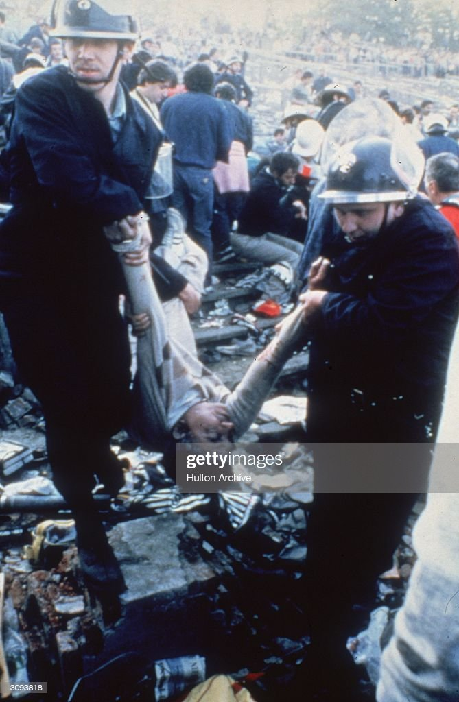 Police carry away an injured fan at Heysel Stadium in Brussels after violence resulted in 38 deaths and 437 people injured prior to the European Cup...