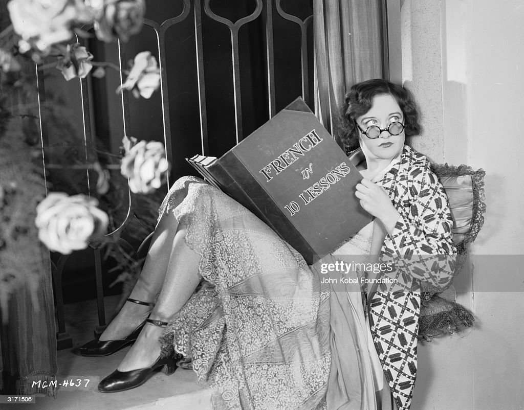 American actress Joan Crawford (1904 - 1977) reading a book entitled 'French in 10 Lessons'.