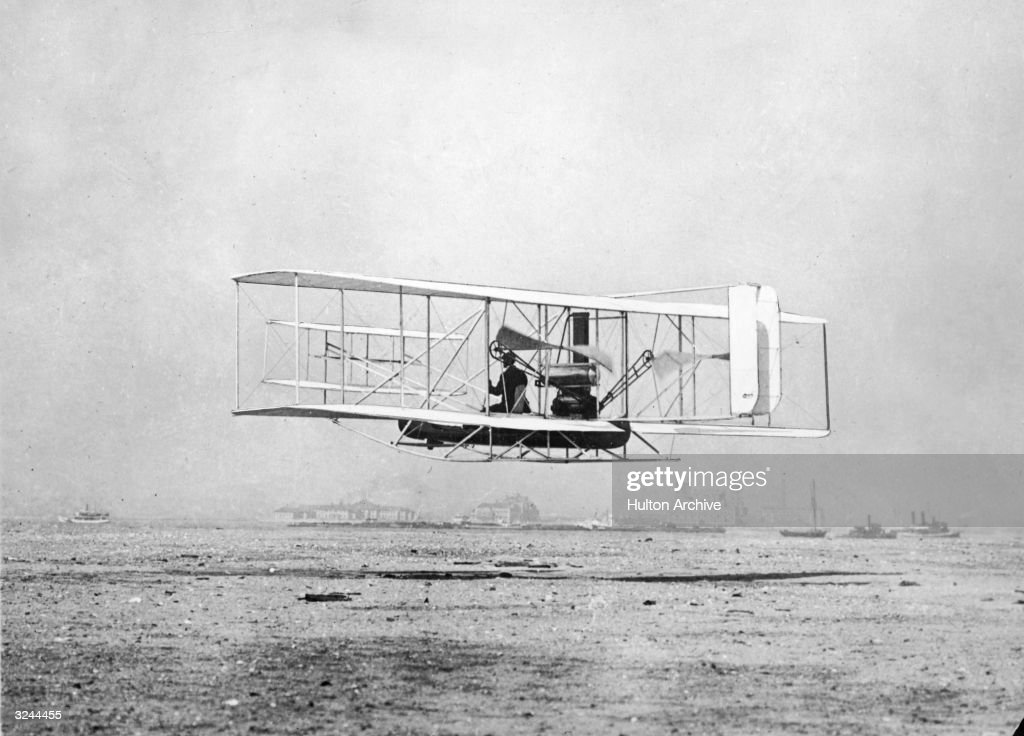 American aviation pioneer Wilbur Wright demonstrates the 'Flyer' biplane he designed with his brother Orville, over water, New York Harbour. Flying past Governors Island. A canoe is mounted under the plane in case of emergency landing.