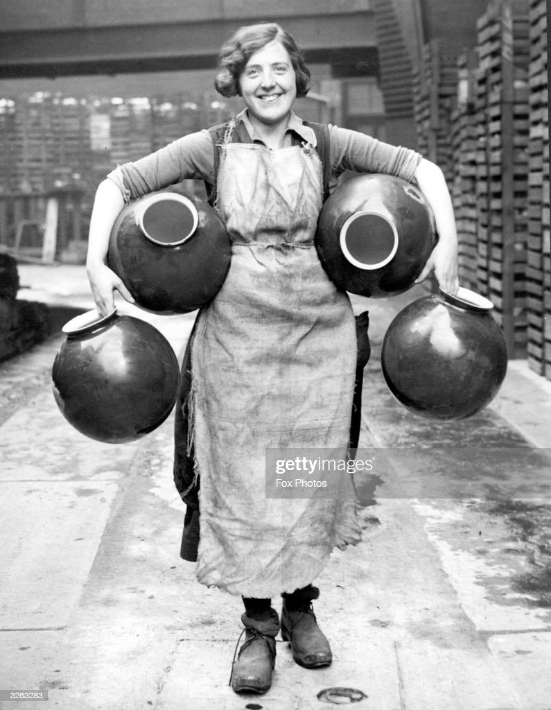 A factory worker at the glass factory at Morley near Wakefield where the Belisha Beacons are manufactured carrying four beacon glasses