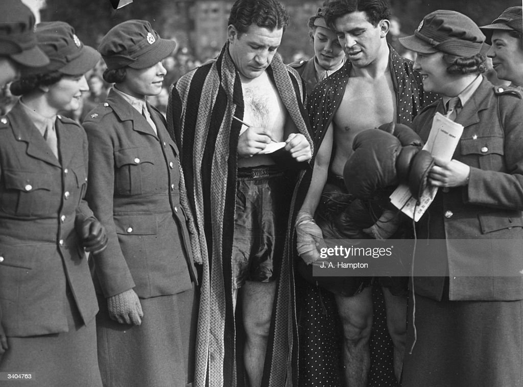 Jack Hyams (right) Southern area middleweight boxing champion and Jock McAvoy British Empire middleweight boxing champion signing autographs for Auxiliary Territorial Services (ATS) girls.