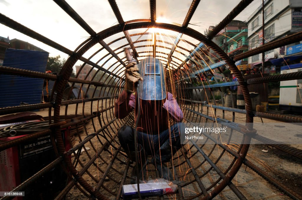 CHAUDHARY, 29yrs old migrated from sunsari, welding iron pillar for on-going Bridge expansion work supported by China AID at Kalanki, Kathmandu, Nepal on Monday, July 17, 2017. The workers used to earn daily wage of NRs. 800 (US$ 8) per day.
