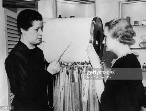 A beautician operates a facial line detector invented by Helena Rubinstein The device contains a number of powerful lenses and is used to detect...