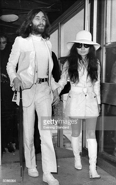 Singer and songwriter John Lennon and his wife artist Yoko Ono both dressed in white at London Airport
