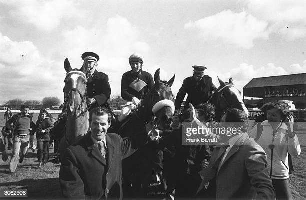 British jockey Tommy Stack on Red Rum is led in at Aintree after winning the Grand National making Red Rum the first horse to win three Nationals