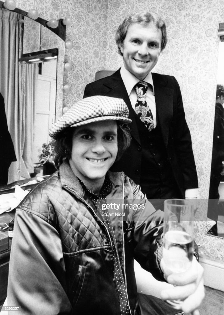 British pop singer and pianist Elton John has a glass of champagne backstage with footballer Bobby Moore (1941 - 1993).