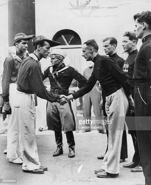 British fascists shaking hands with Italian fascists in their distinctive uniform The 50 Italians are in England on a reciprocal visit