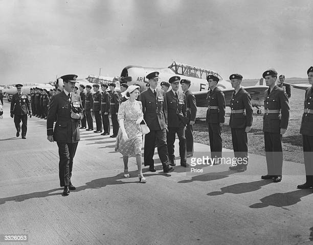HRH Princess Elizabeth inspecting RAF flight wing personnel in front of their aircraft at the RAF College Cranwell