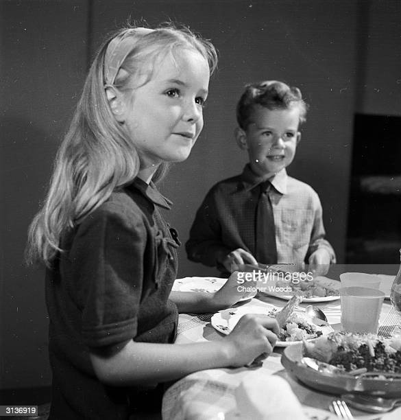 Two children sitting down to a family dinner