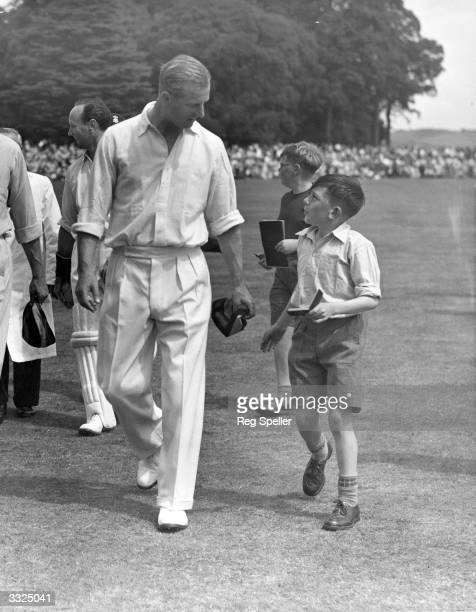 Prince Philip the Duke of Edinburgh is accosted by a young autograph seeker at a celebrity cricket match against the Duke of Norfolk's team at...