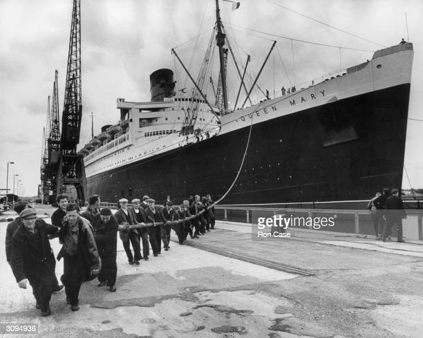 Workmen drag the veteran Cunard White Star liner Queen Mary into the dry dock at Southampton for a process of underwater cleaning She will also be...