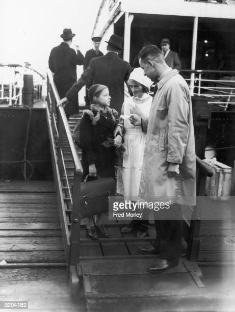 A German Jewish girl Helga Samuel with an identity tag is met off the boat at Harwich by a representative involved in the 'Kindertransport' which...