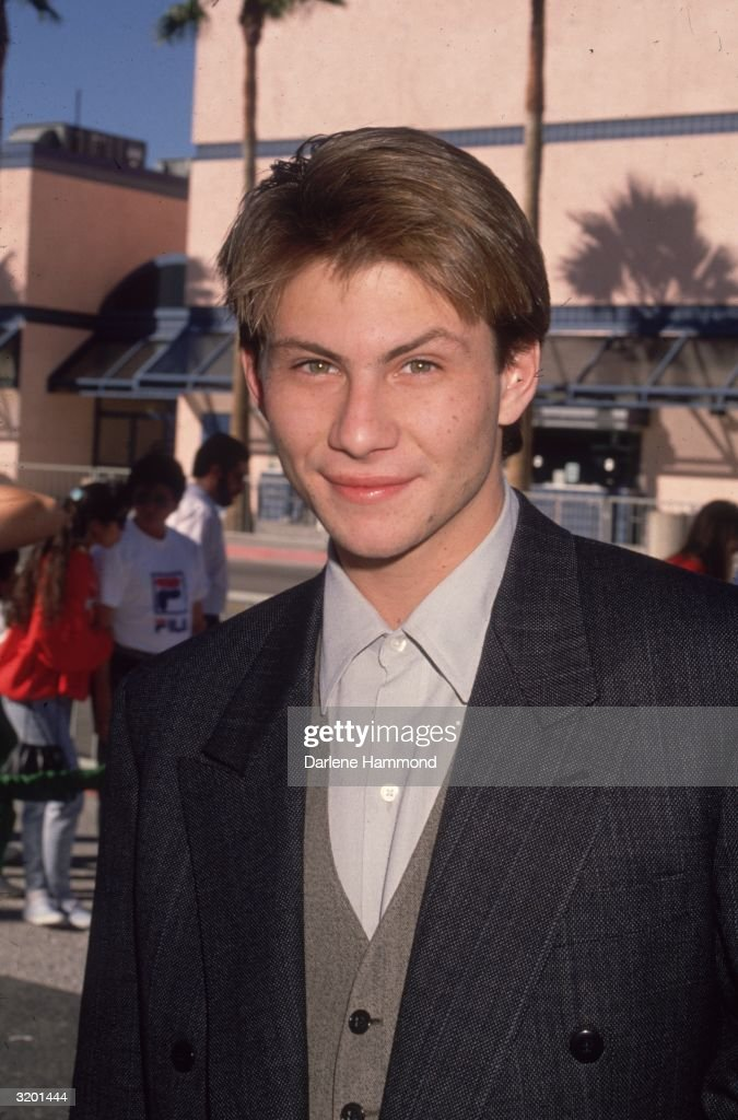 Headshot of American actor Christian Slater, outdoors. He is wearing a gray suit jacket over a brown vest and gray shirt.