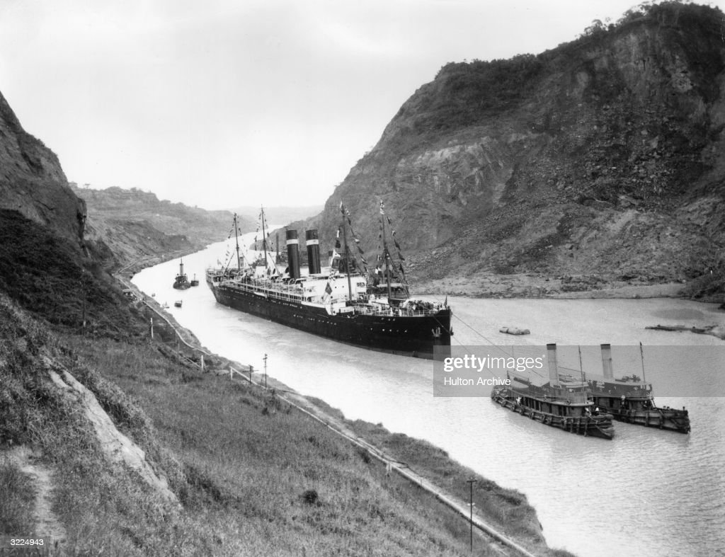 A pair of tugboats pull the SS 'Kroonland' through the Cucaracha slide, heading south along Culebra Cut on the Panama Canal.