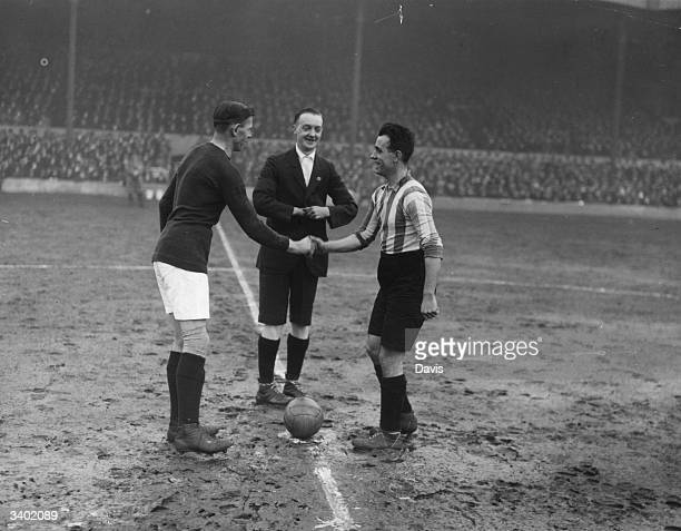 Arsenal and Port Vale captains Buchan and Connely shake hands in font of the referee G Ward before the kick off as Arsenal play Port Vale in an FA...