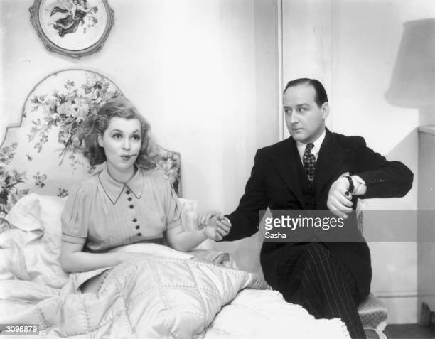 Germanborn actress Lilli Palmer has her temperature and her pulse taken by a doctor in a scene from Ian Hay's comedy 'Little Ladyship' at the Strand...